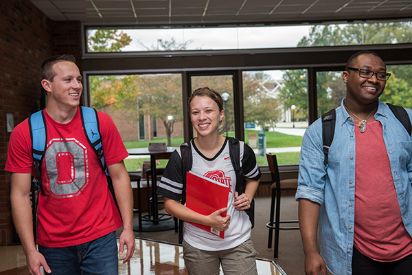 Three students walk together through common area